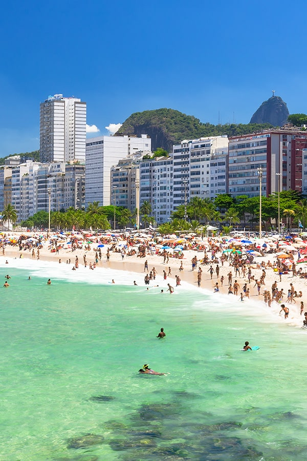 A beach in Rio with a row of modern buildings behind it and Christ the Redeemer in the distance.