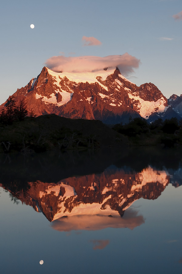 Snow-capped mountain peaks reflected in a lake in Torres del Paine National Park.