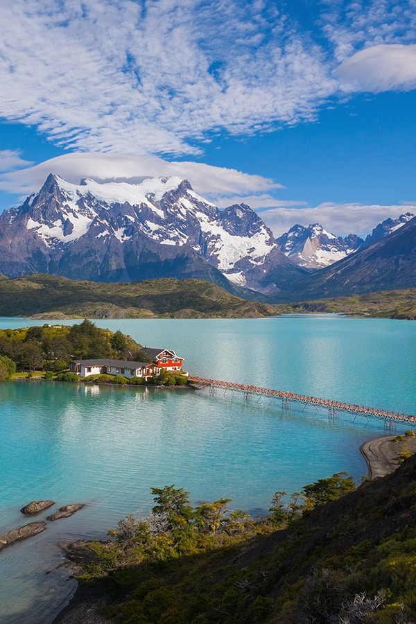 Scenic houses on a blue-tinted lake with snow-capped mountains at Torres del Paine National Park.