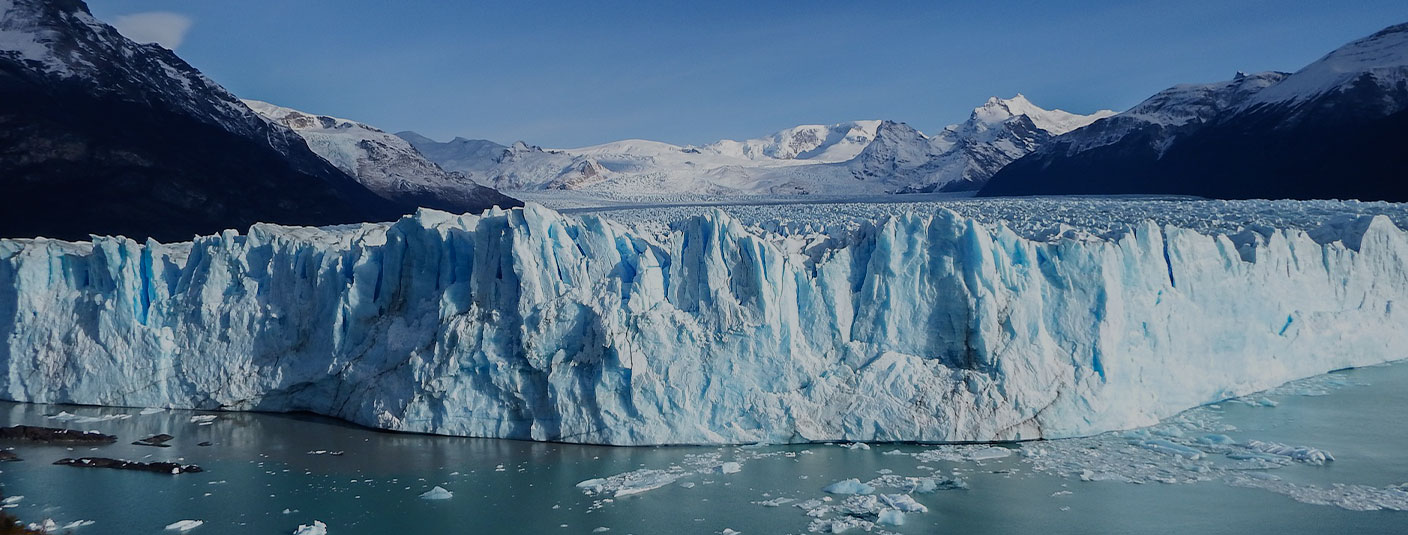 Panoramic view of the blue-tinted Perito Moreno glacier and surrounding mountains.