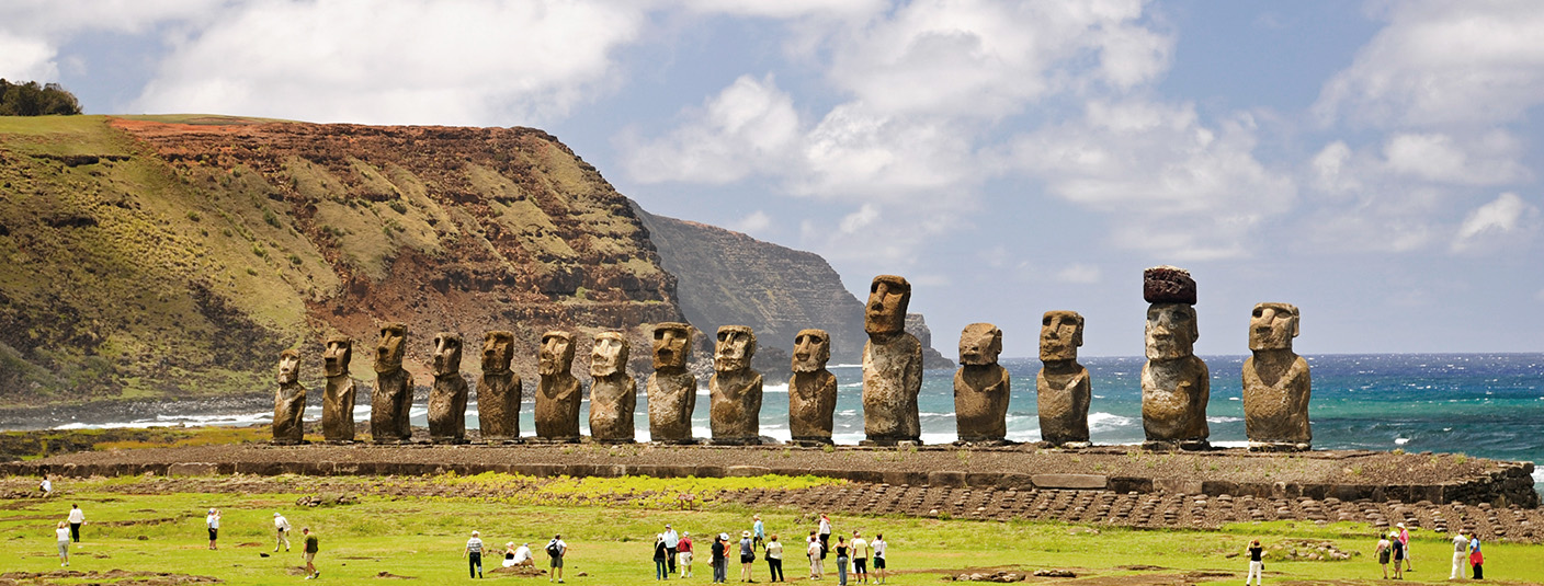 Visitors admiring a line of moais, the monolithic human figures found on Easter Island.