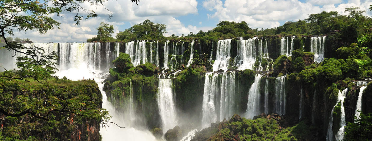 Lush green vegetation and waterfalls at Iguazu Falls, the largest waterfall in the world.