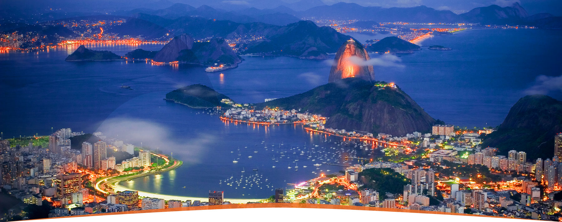 Rio de Janeiro lit up at night, with the iconic Sugarloaf Mountain towering over the city.