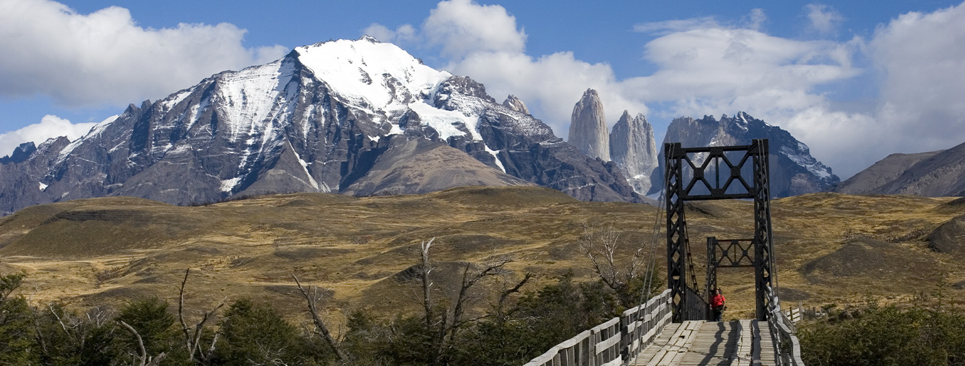 A visitor crossing a bridge in Torres del Paine National Park, with a couple of the peaks visible.