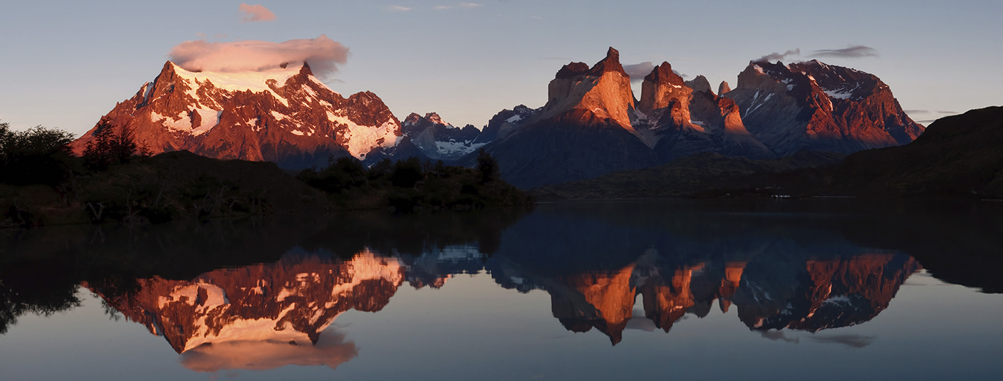 Snow-capped mountains and the back of the iconic peaks of Torres del Paine reflected in a lake.